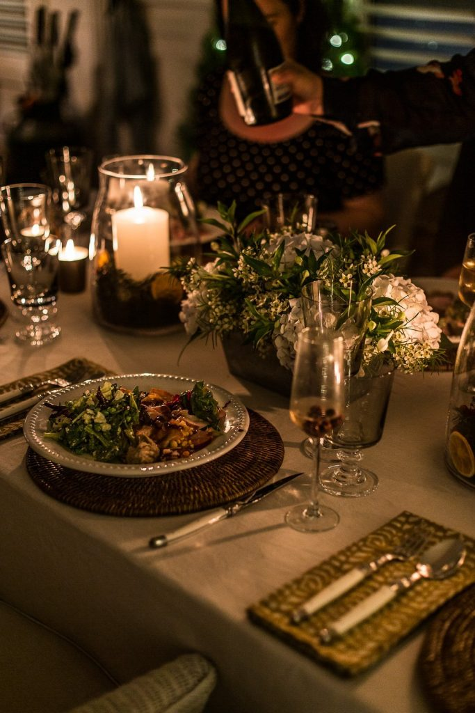 Christmas table setting with food, flowers and candles